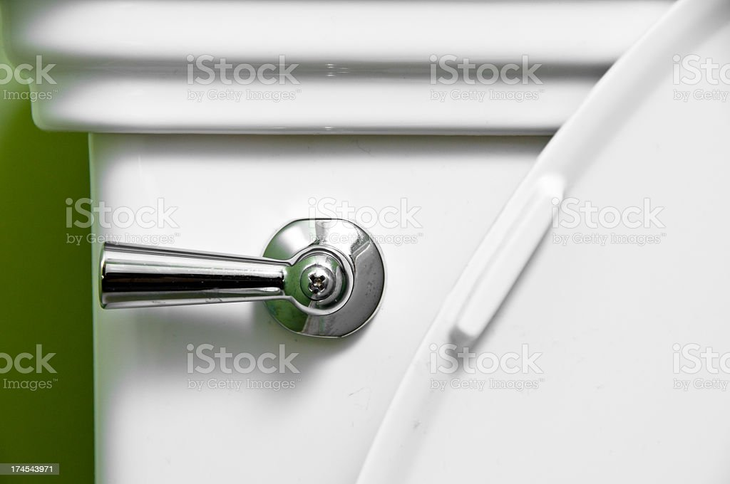 A shiny handle in a white toilet stock photo
