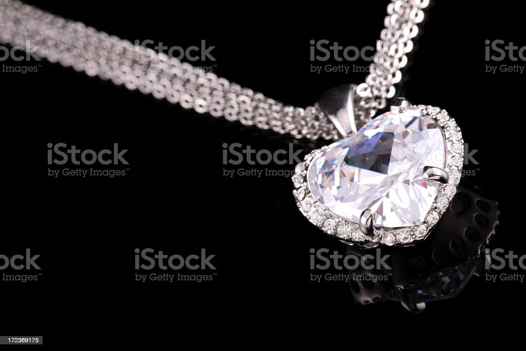 Shiny, heart-shaped diamond pendant on silver colored chain  stock photo