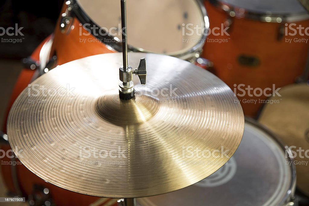 shiny hi-hat cymbals on stand with wooden orange drum-kit stock photo