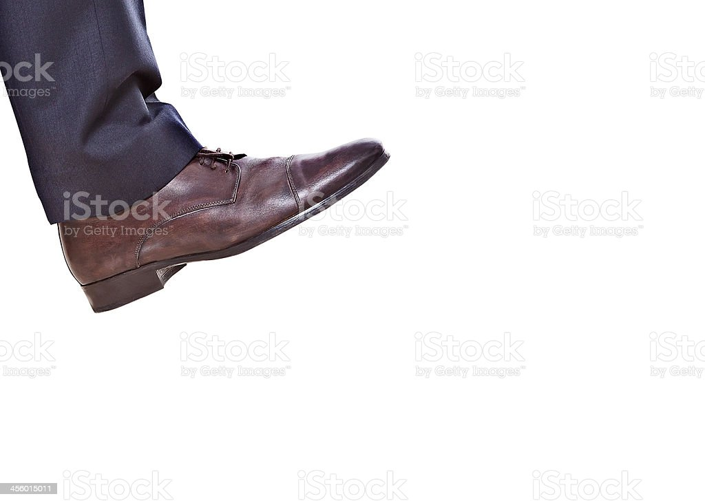 Shiny leather brown mens shoe and blue trouser leg stock photo