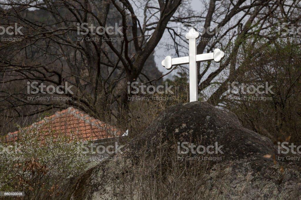 Shiny, metal Christianity cross on the rock outdoors stock photo