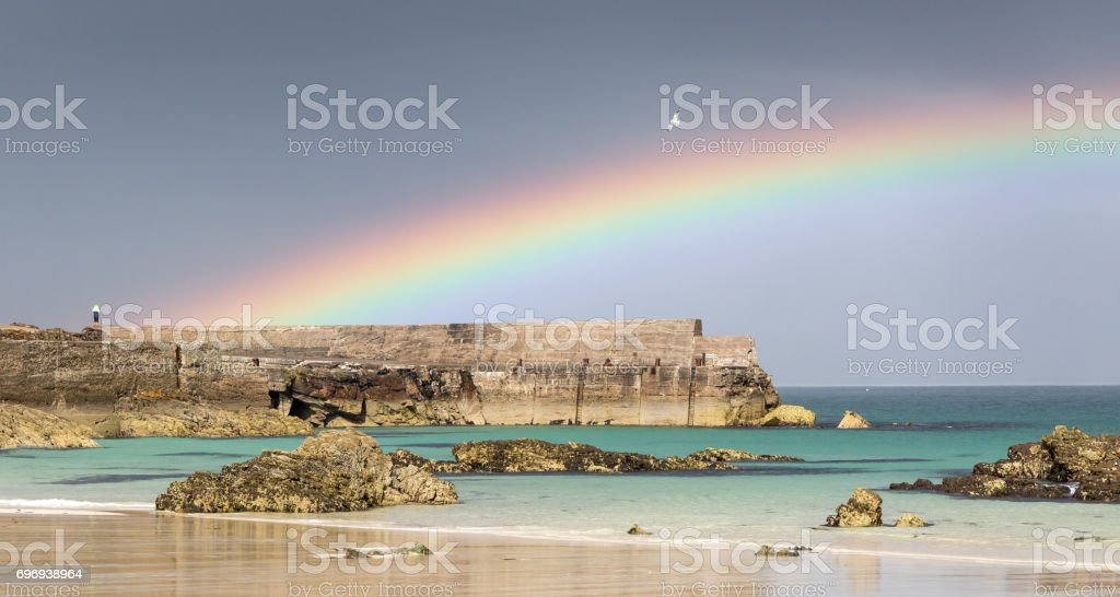 Shiny rainbow over harbor and beach stock photo