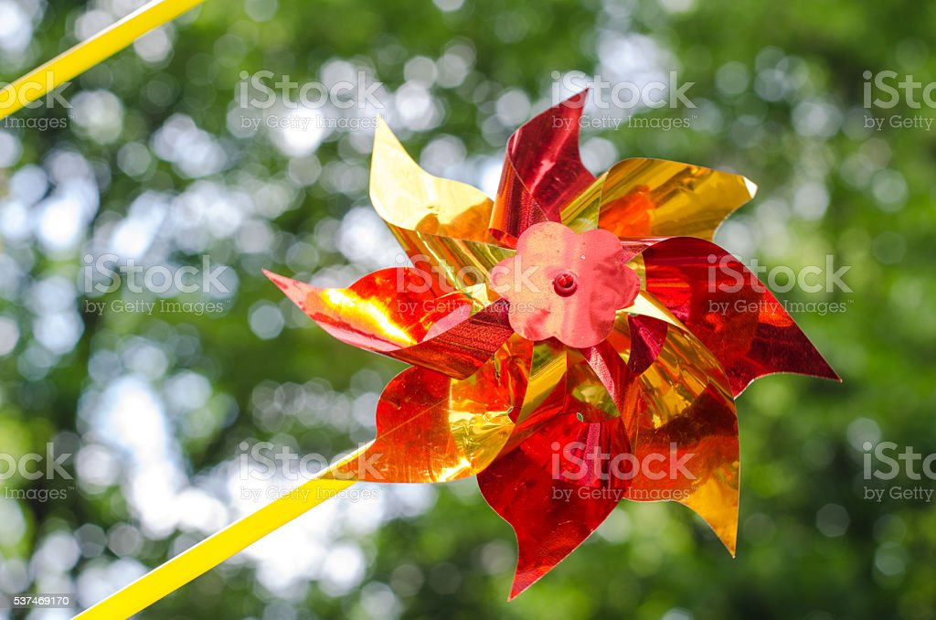 Shiny red and yellow pinwheel toy on summer background stock photo