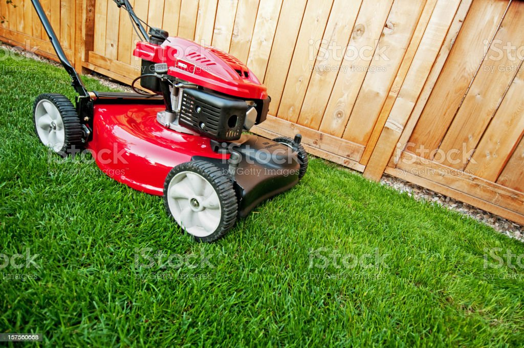 Shiny red lawnmower is ready for business stock photo
