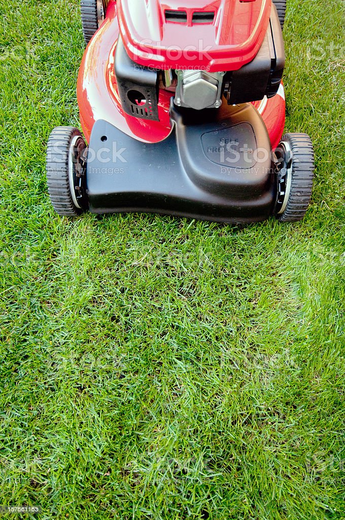 Shiny red lawnmower is ready to cut stock photo