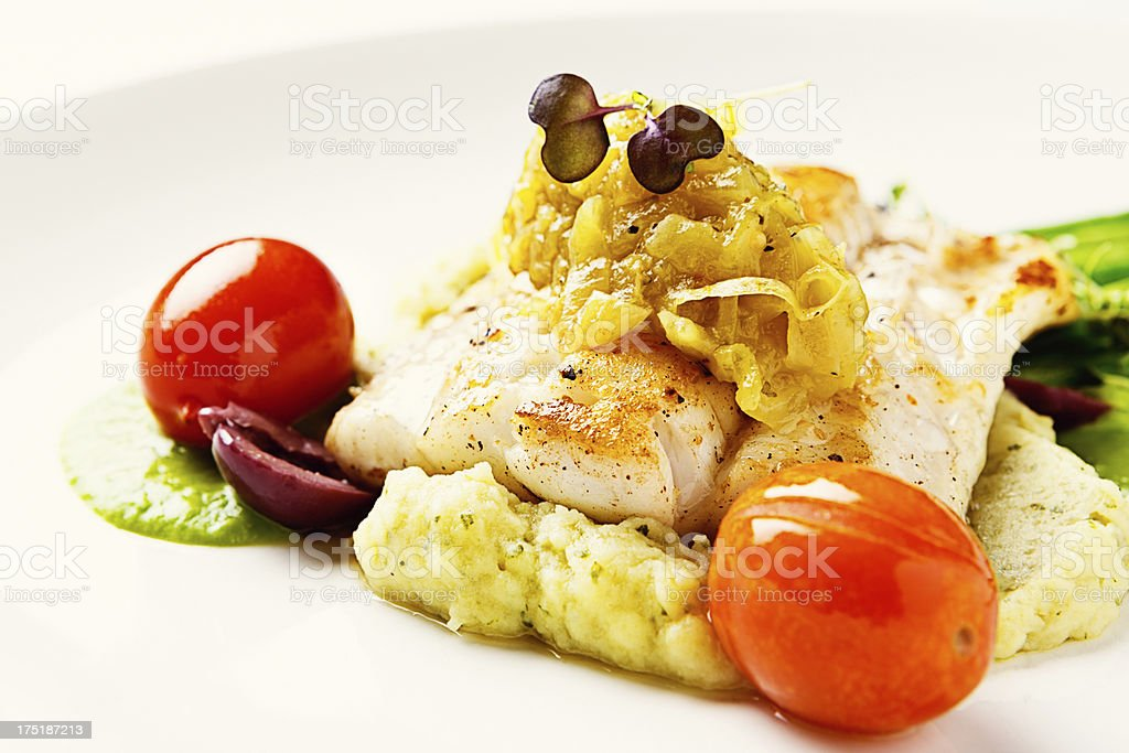 Shiny roasted tomatoes accompany garnished grilled fish in restaurant entree stock photo