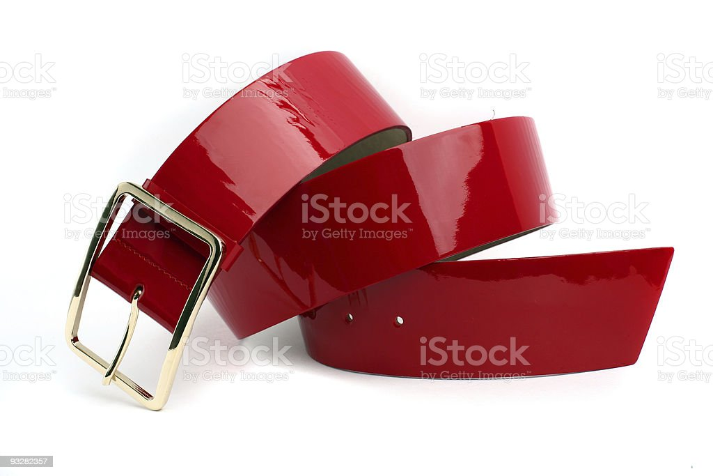 A shiny rolled up red belt with a gold buckle on white  stock photo