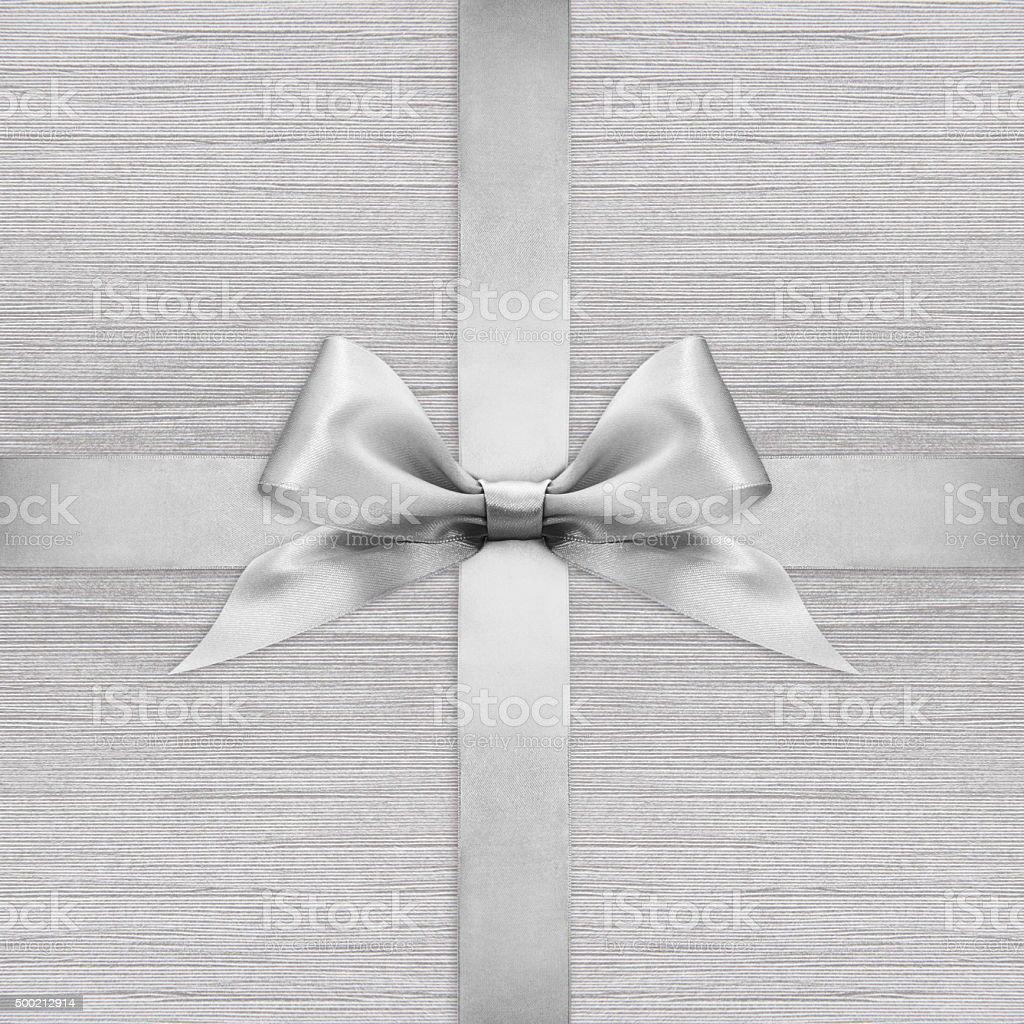 Shiny silver satin ribbon bow on argent background stock photo