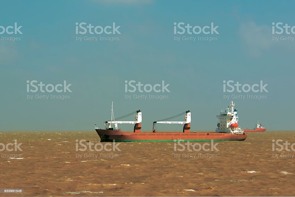 ship at anchor in the yellow water of the Yellow sea stock photo