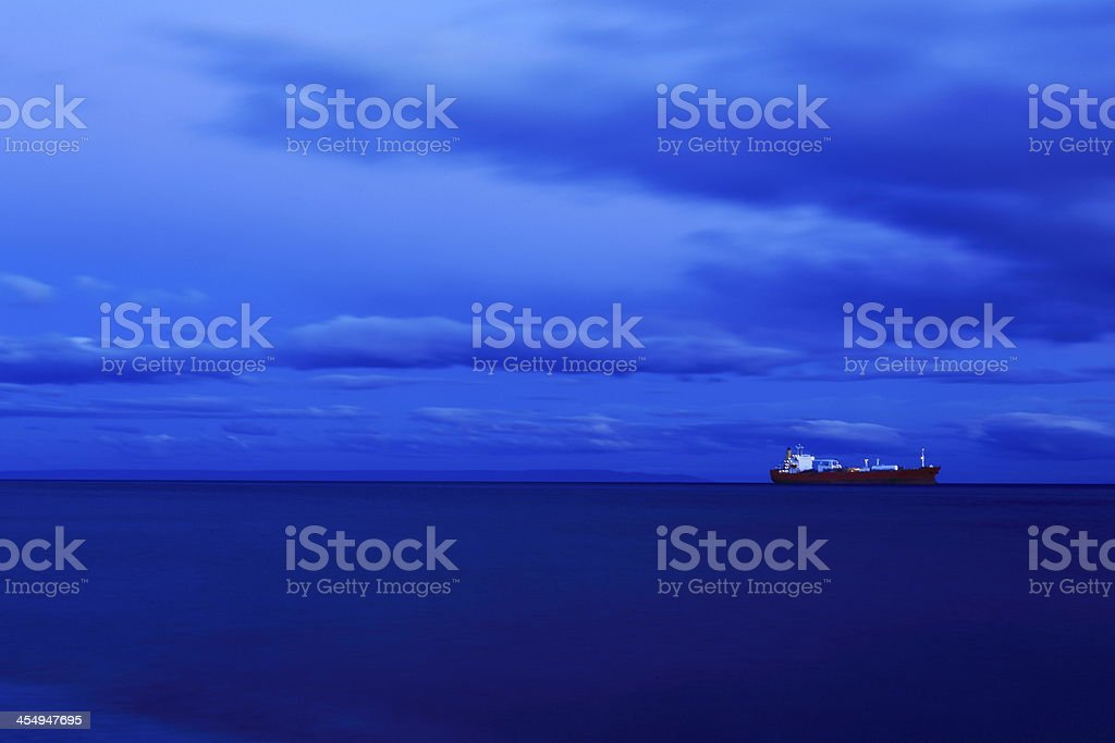 Ship at night dramatic sky cloudscape and sea stock photo