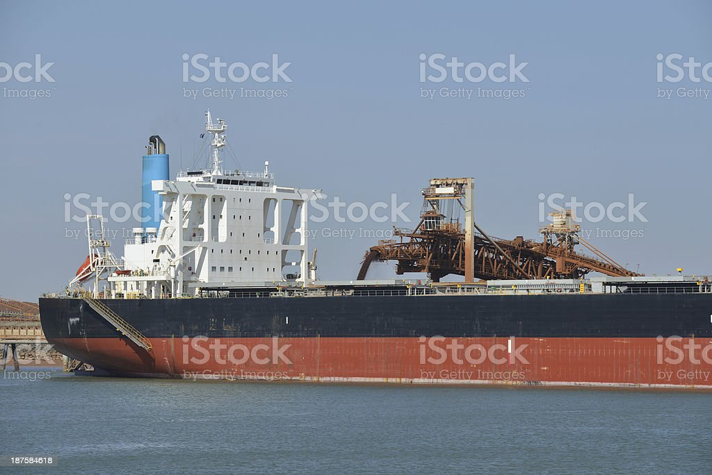 Ship being loaded with ore at a harbour. stock photo
