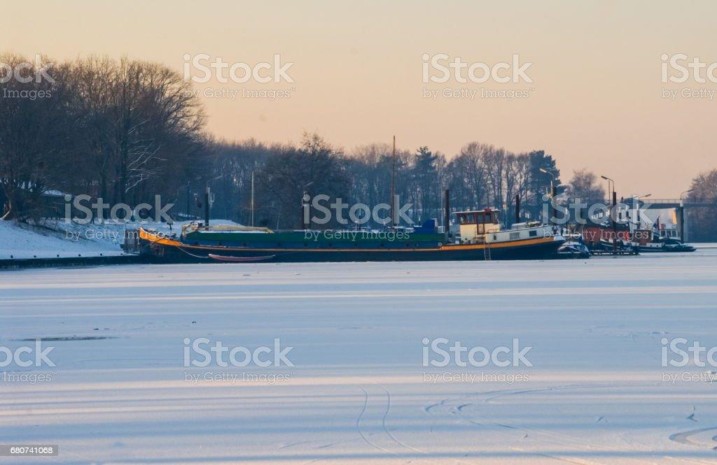 Ship boat caught in frozen sea icebound ice snow harbor stock photo