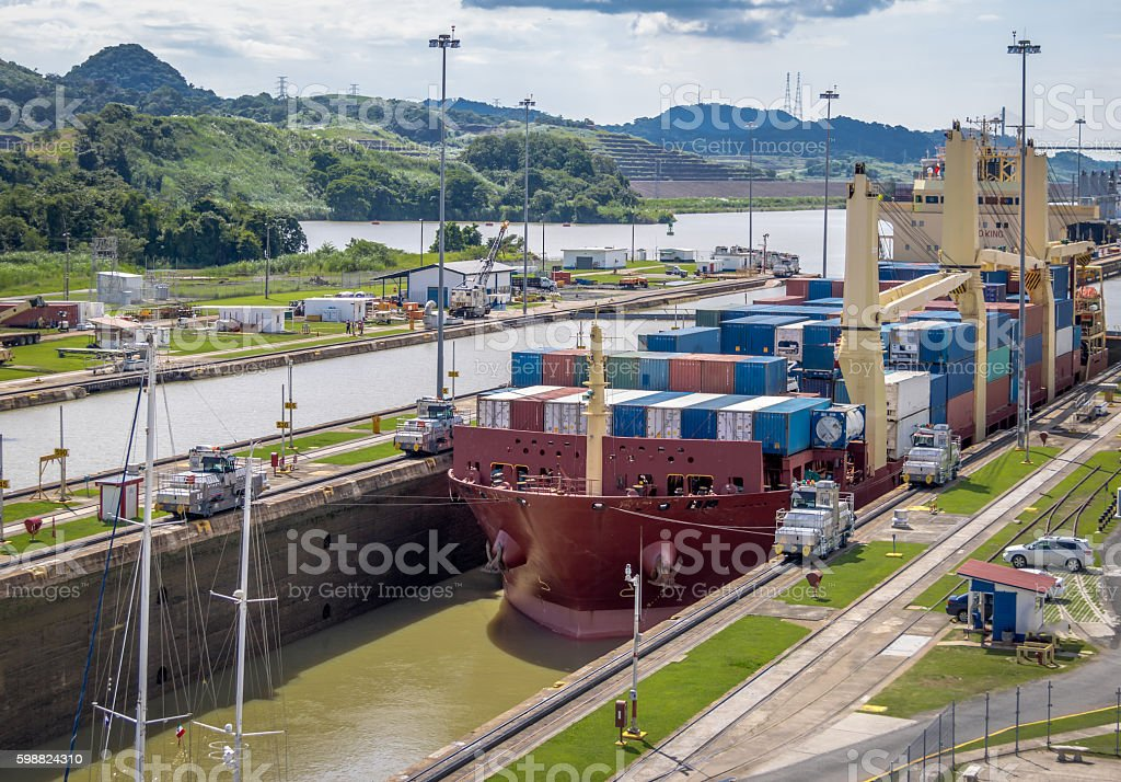 Ship crossing Panama Canal being lowered at Miraflores Locks stock photo