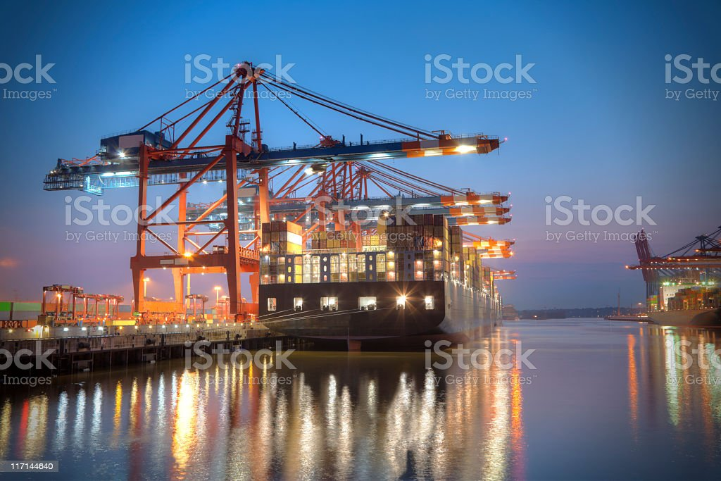 A ship docked at a harbour at night time stock photo