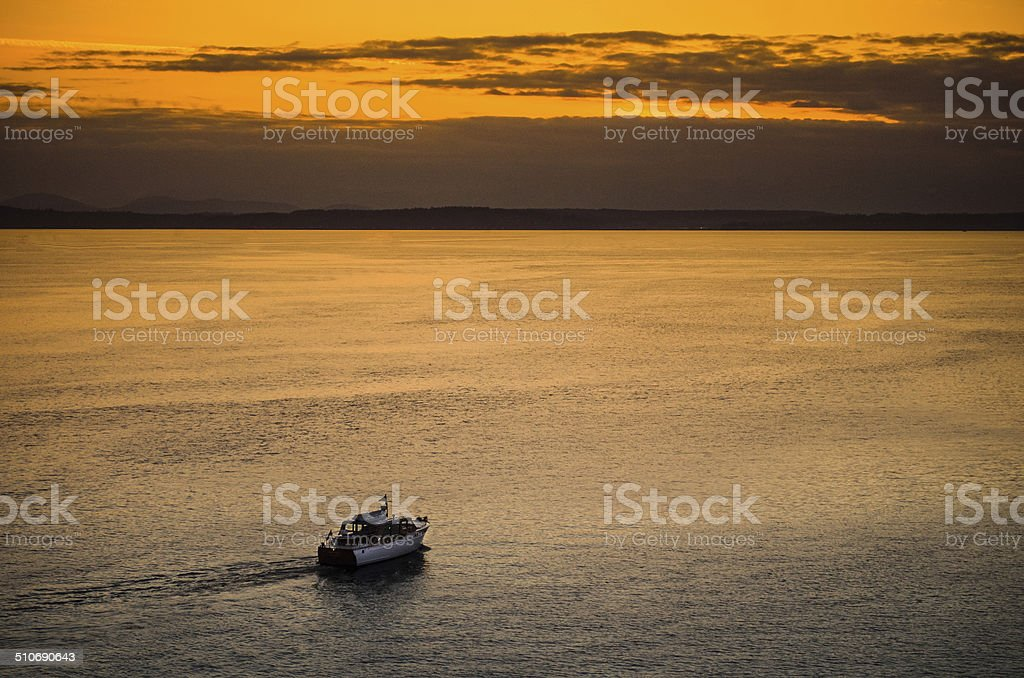 Ship going into horizont in golden sunset stock photo