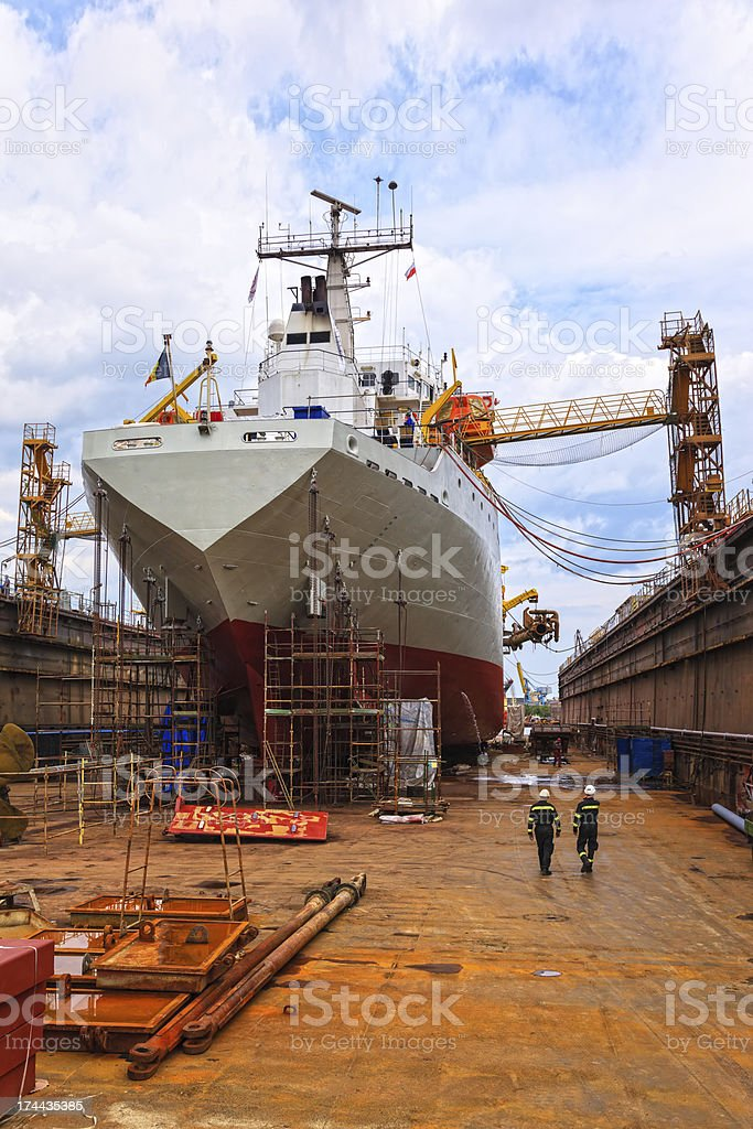 Ship in dry dock with construction workers walking around stock photo
