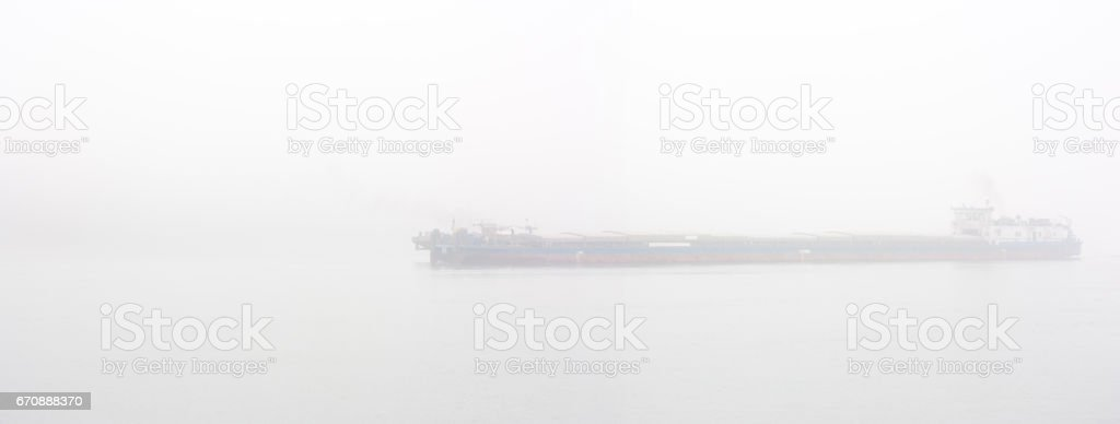 Ship on a river in heavy fog stock photo