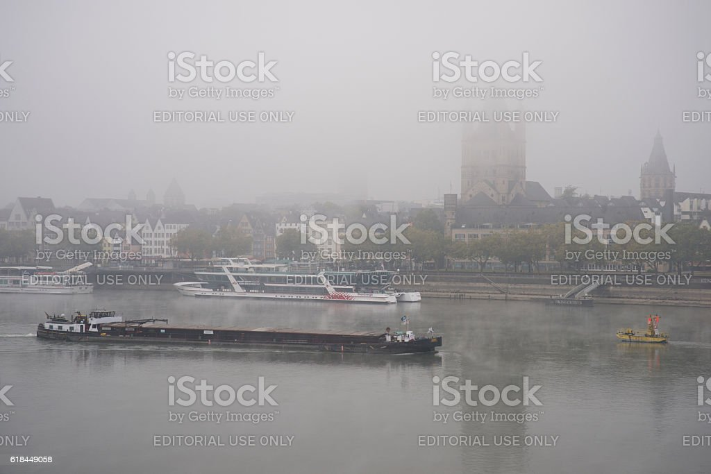 Ship on foggy Rhine river passes church in Cologne stock photo