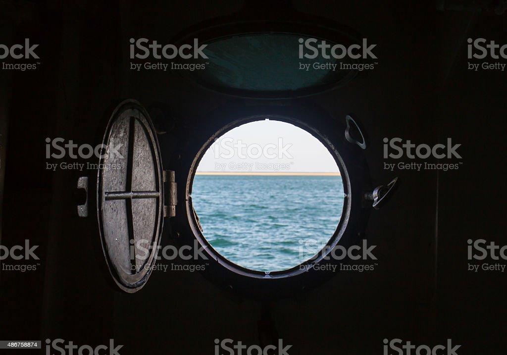 ship porthole on wooden wall stock photo