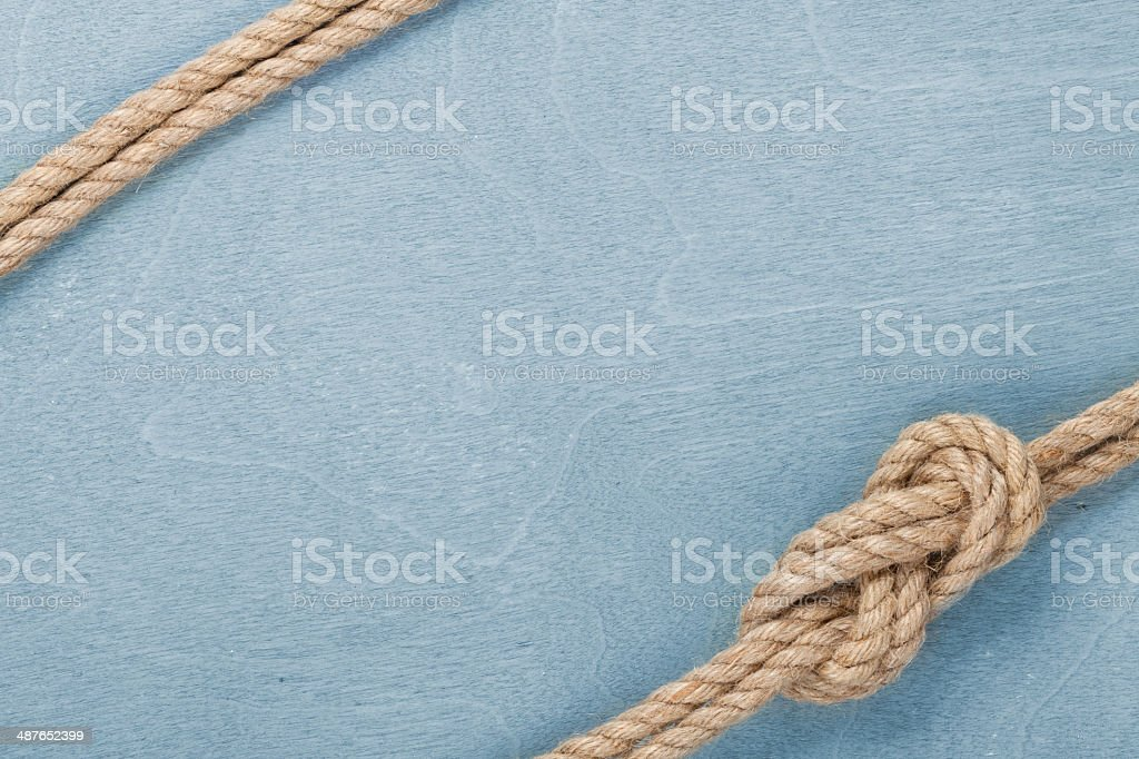 Ship rope knot on wooden texture background stock photo