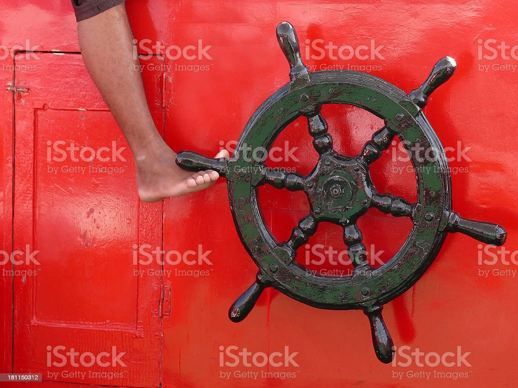 ship steering wheel on red with foot royalty-free stock photo