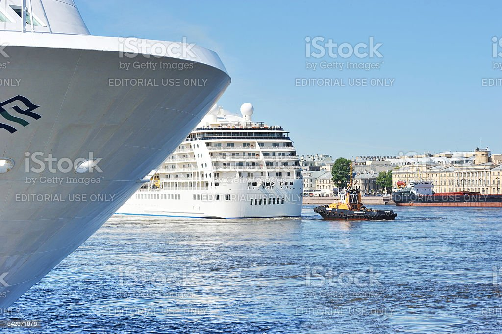 ship tug turning a large ocean liner stock photo