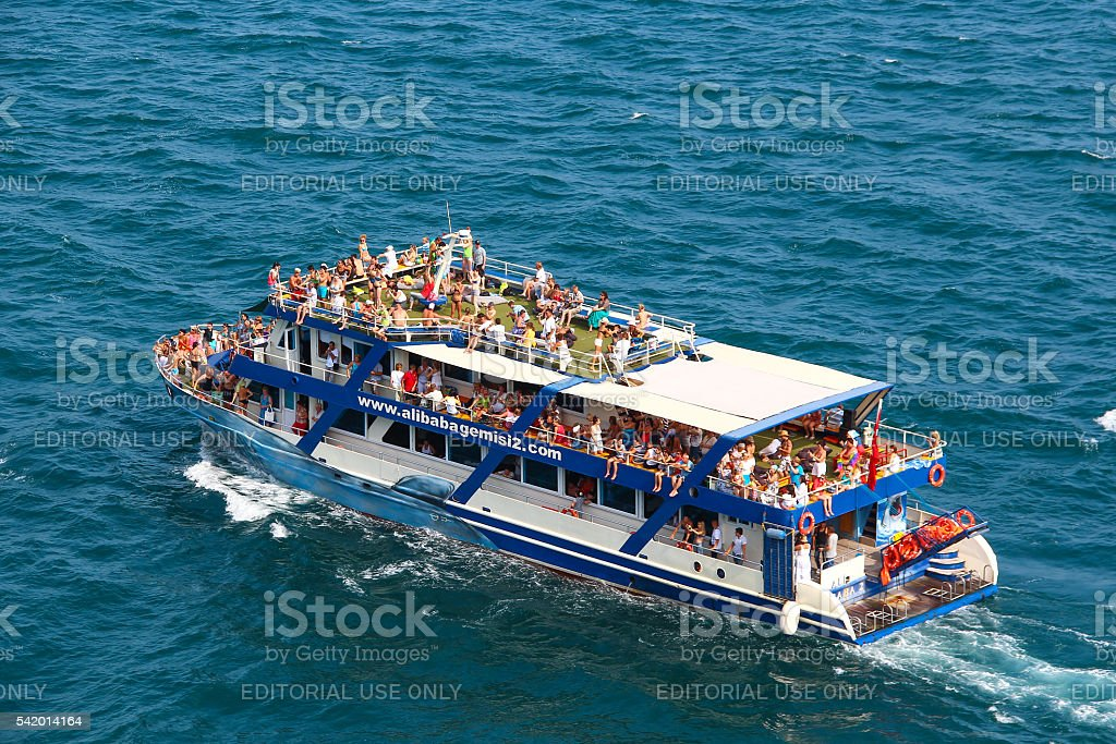 Ship with holidaymakers and tourists sunbathing in the sea. stock photo