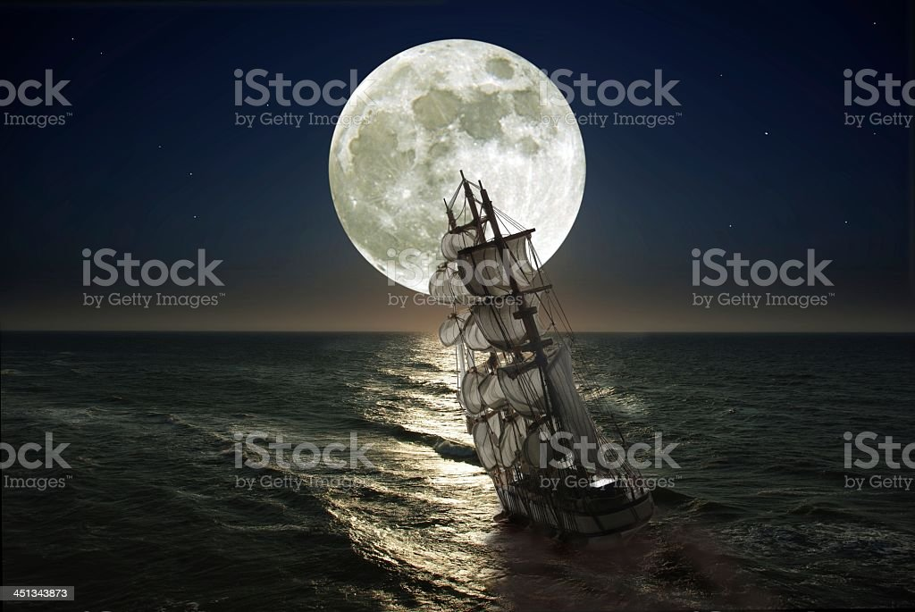 Ship with sails leaning in sea as moon rises stock photo