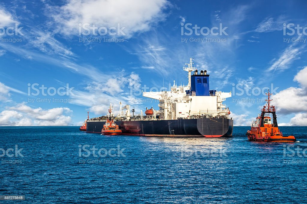 Ship with Tugboats stock photo