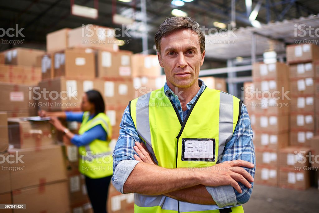 Portrait of a worker standing in a large warehouse full of boxes with...