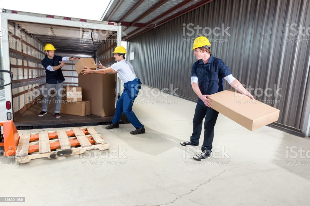 Shipping company employees throwing boxes stock photo