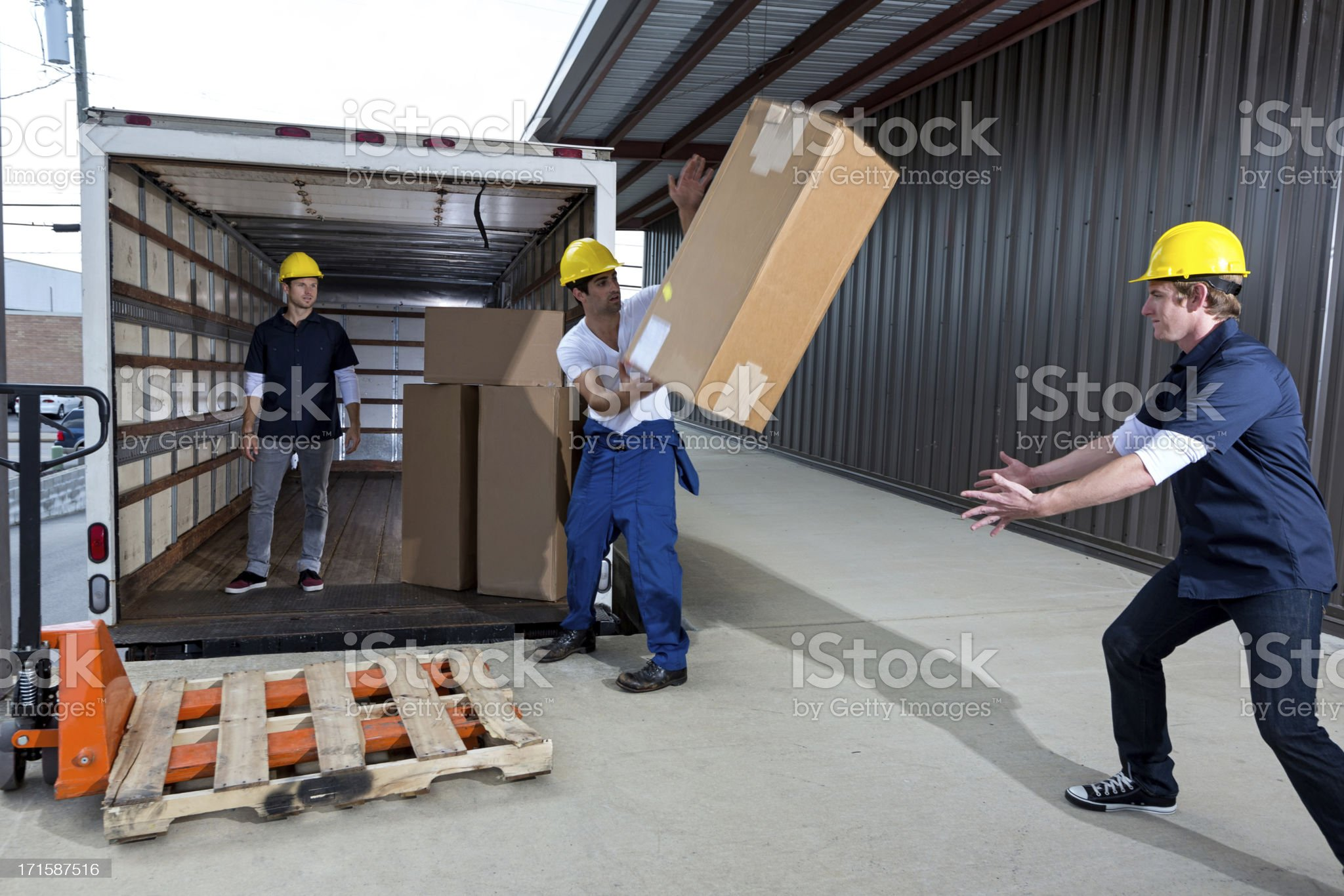 Shipping company employees throwing boxes royalty-free stock photo
