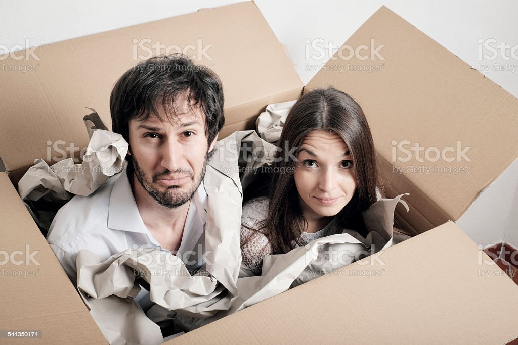 Shipping people in a box - puzzled young couple stock photo