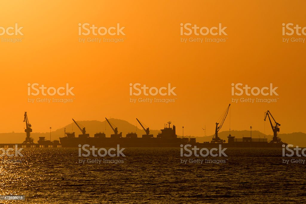 Shipping port in the sea with sunset sky stock photo