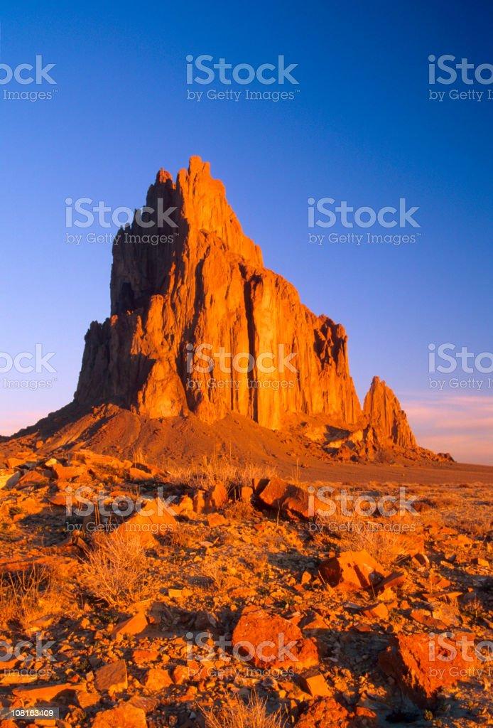 Shiprock in Desert Against Blue Sky stock photo