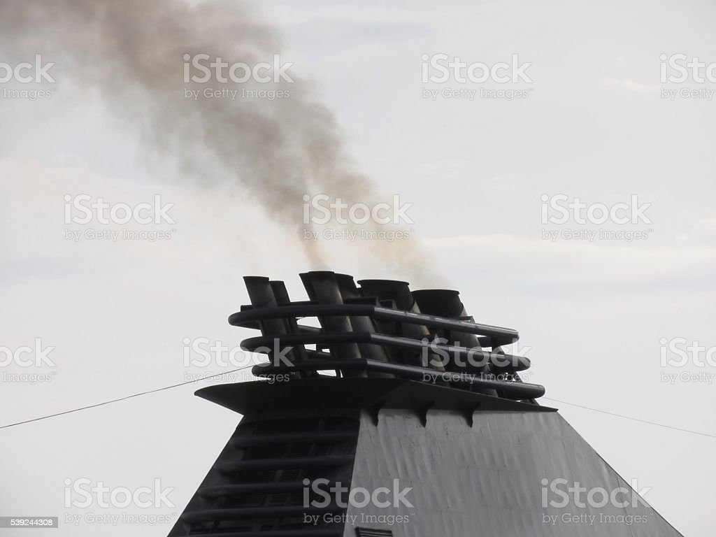 Ships funnel emitting black smoke in the sky stock photo