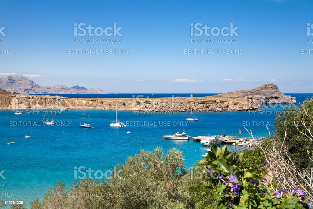 Ships on the Mediterranean blue lagoon. Greek rocky cliffs and the coast of the island of Rhodes. Beach and harbor. Leisure on the island of Rhodes. stock photo