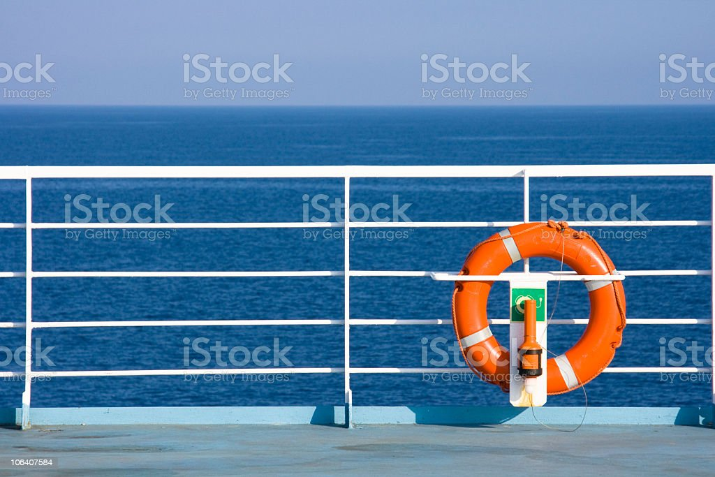 Ships railing with float device with sea in the background royalty-free stock photo