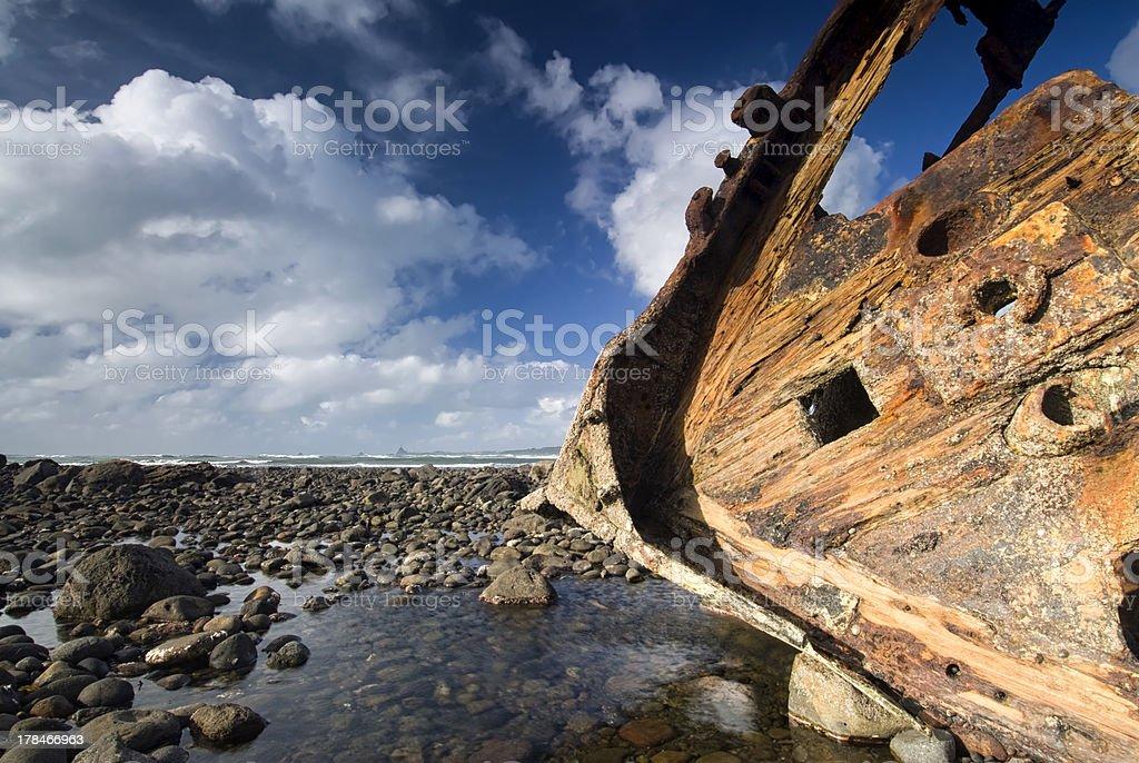 Shipwreck on rocky beach stock photo