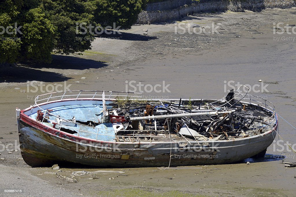 Shipwrecked boat on a beach stock photo