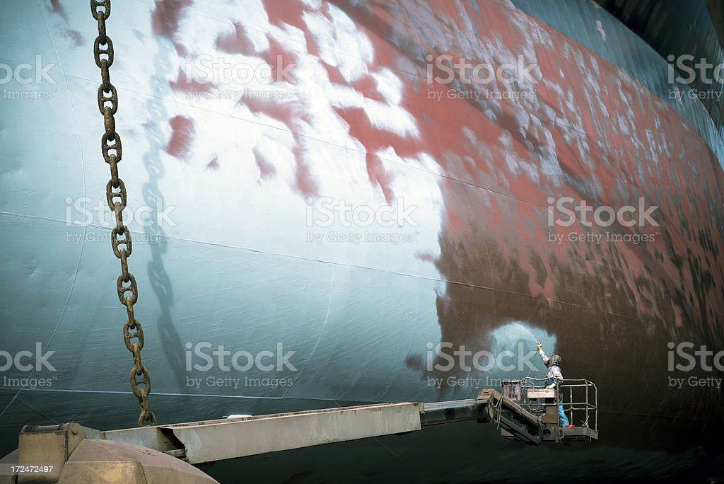 Shipyard worker painting a ship's deck stock photo