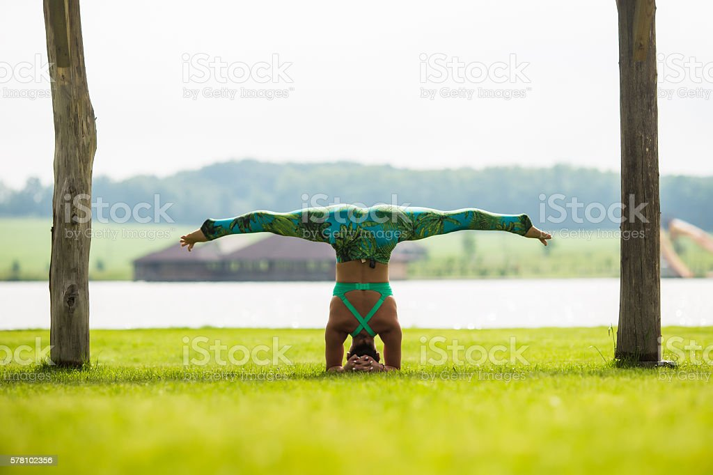 shirshasana. Yoga girl training outdoors on nature background. Yoga concept. stock photo