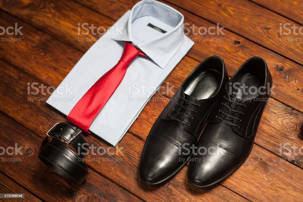 shirt, shoes and belt on a wooden background stock photo