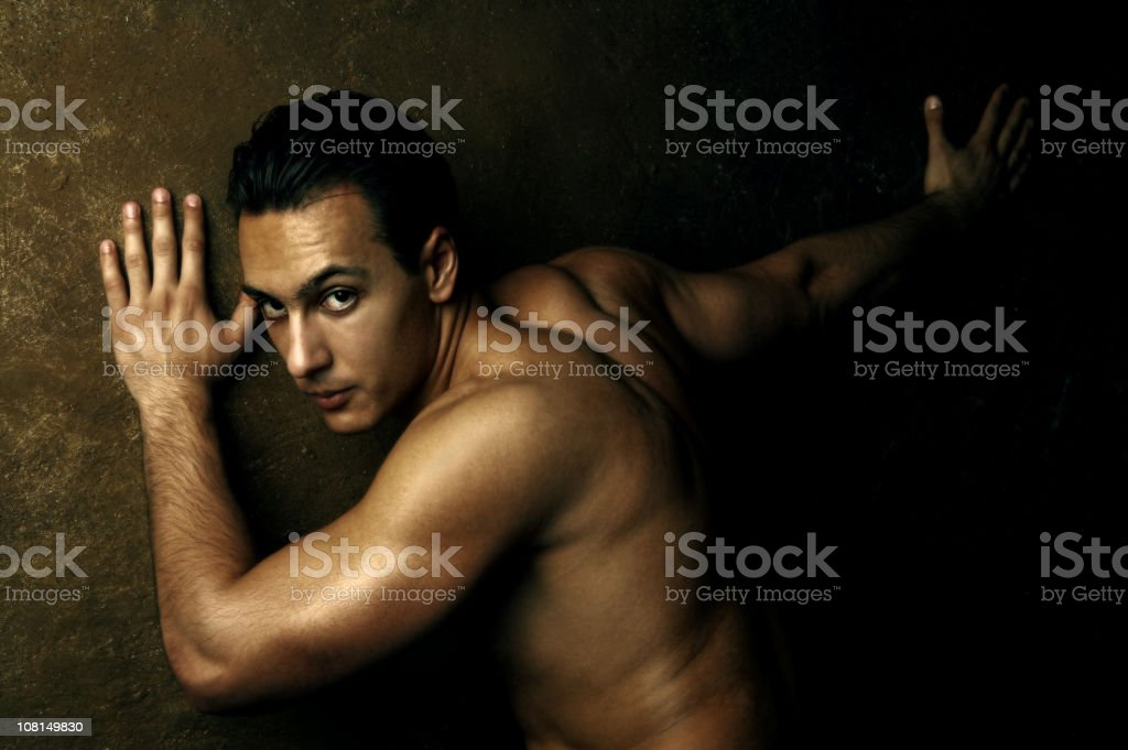 Shirtless and Muscular Man  Leaning with Hands on Wall royalty-free stock photo