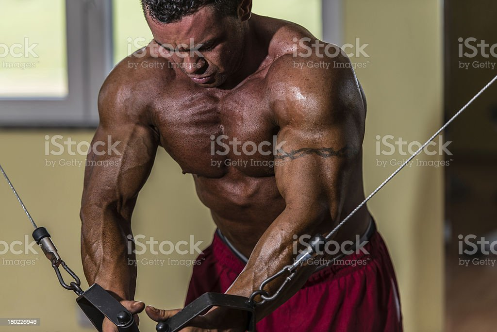 shirtless body builder doing standing press white cable for chest royalty-free stock photo