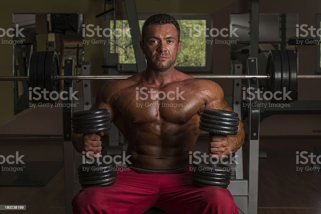 shirtless body builder posing with dumbbell at the bench royalty-free stock photo