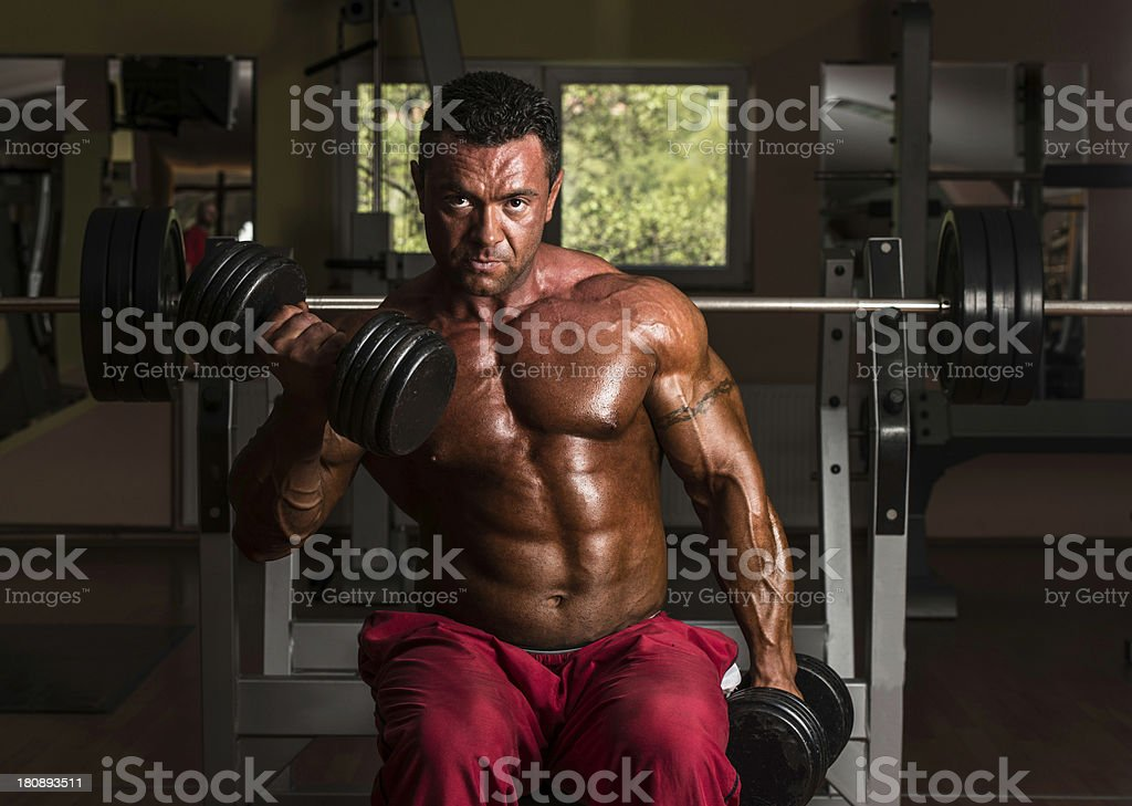 shirtless bodybuilder doing heavy weight exercise for biceps royalty-free stock photo