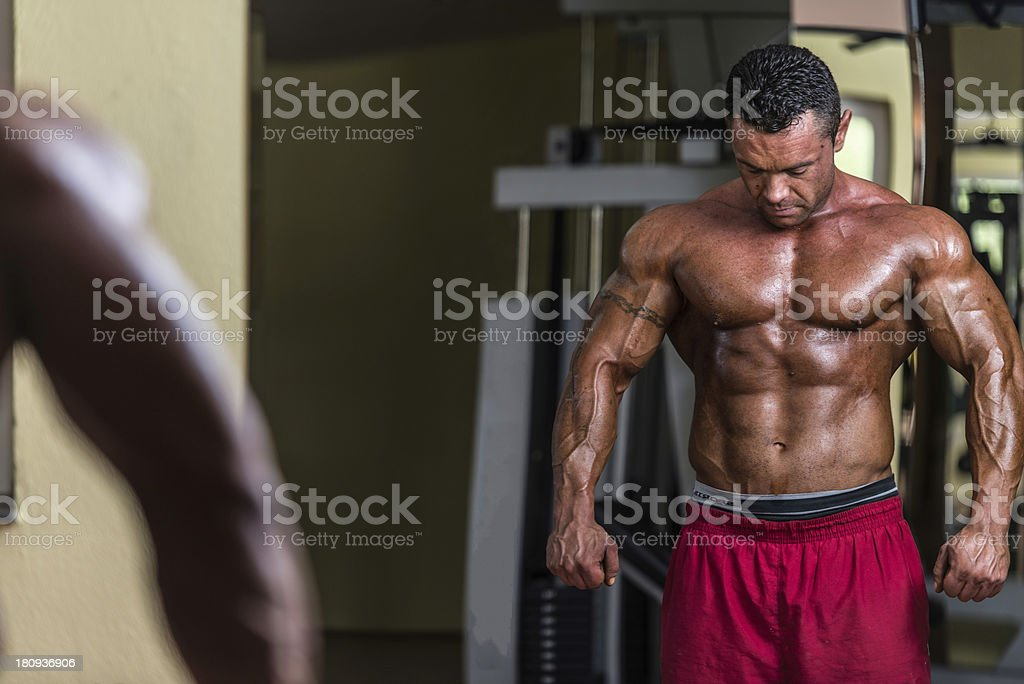 shirtless bodybuilder posing at the mirror royalty-free stock photo