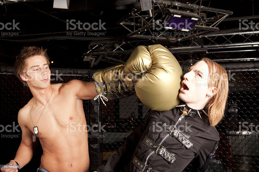 Shirtless boxer punching punk with oversize boxing glove royalty-free stock photo
