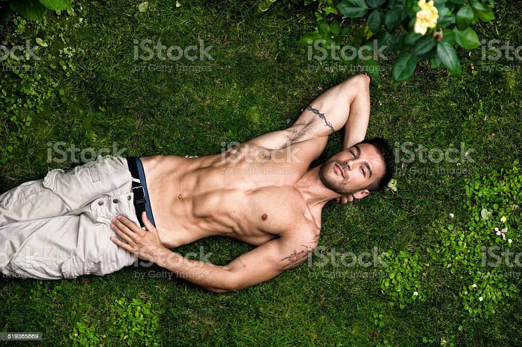 Shirtless fit male model relaxing lying on the grass stock photo